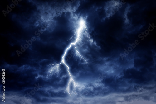 Fotografie, Obraz A lightning strike on a cloudy dramatic stormy sky.