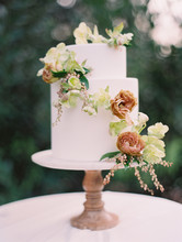 Close-up Of Wedding Cake Decorated With Flowers On Cake Stand