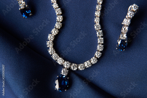 Slika na platnu Close-up of women's platinum necklace and earrings with a diamond and blue precious sapphire stone