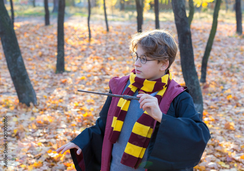 cute young boy in costume of  magician with wand , in round glasses.