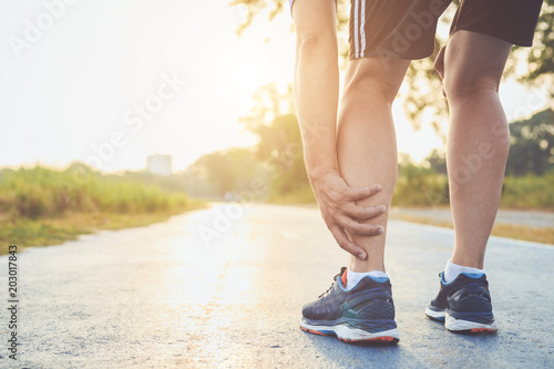 Injury from workout concept : Asian man use hands hold on his ankle while running on road in the park Canvas Print