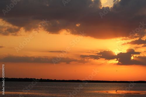 Spoed Foto op Canvas Zee zonsondergang Golden sunset sky with dark clouds and glowing sun, orange sky with water reflection and sun rays