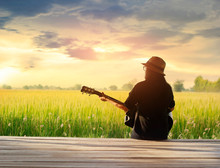 Woman Playing Acoustic Guitar On The Field Rural Sunset Background