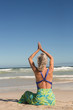 Senior woman with arms raised practising yoga while sitting on shore at beach