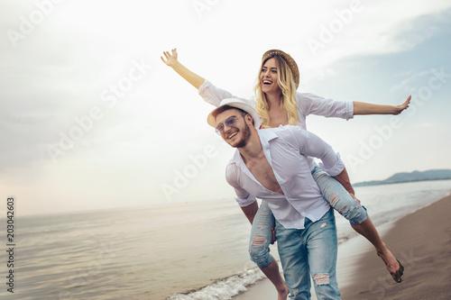 Fototapeta Happy couple in love on beach summer vacations. Joyful girl piggybacking on young boyfriend having fun. obraz