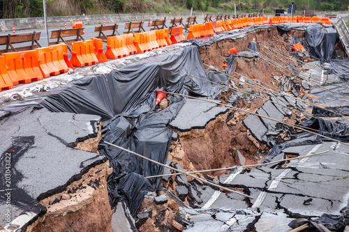 Fototapeta Big damage of asphalt road on the hillside cause of heavy rain and sliding earth