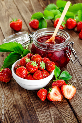 Homemade strawberry jam or marmalade in the glass jar and the basket of ripe strawberries on the wooden table