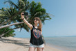 Woman taking selfie at palm on beach