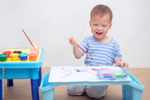 Cute lAsian 18 months / 1 year old toddler boy child painting with brush &  watercolors
