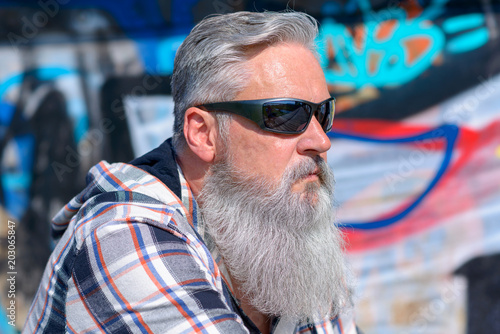 Fotografía  Mature man with long grey beard wearing sunglasses