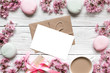 blank greeting card or wedding invitation in frame made of pink cherry blossoming with coffee cup and macarons