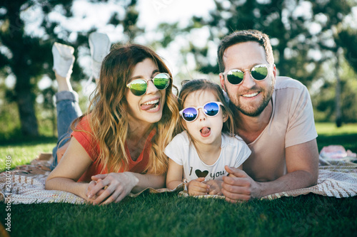 Family with dauhter in sunglasses rest in park.