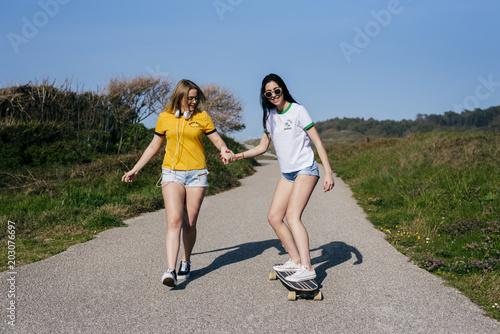 Stylish girlfriends having fun on rural road