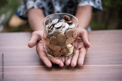 Fotografía  Hand  putting coins in jar with money stack step growing growth saving money