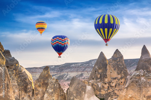 Three bright multi-colored hot air balloons flying in sunsrise sky Cappadocia, Turkey