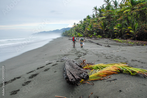 In the early morning, two hikers take the way to Corcovado on the black sand beach of the Osa peninsula in Costa Rica Tablou Canvas