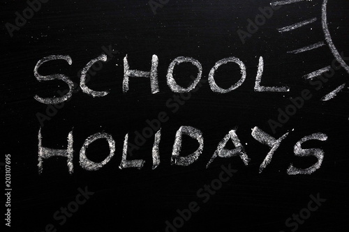 Valokuva  School holidays text and sun drawing on chalkboard