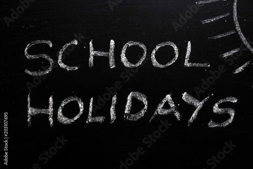 Fényképezés  School holidays text and sun drawing on chalkboard