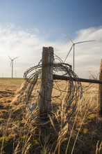Barbed Wire On Wooden Fence Against Windmills And Cloudy Sky At Farm