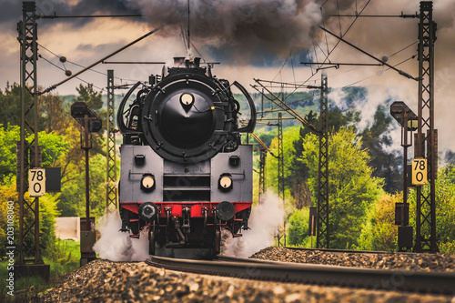 Steam locomotive at full throttle in the countryside