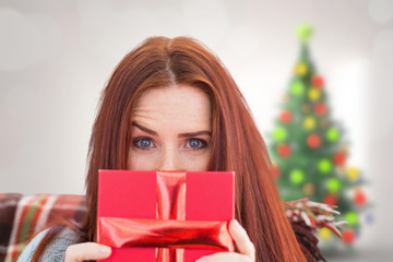Woman holding gift against ...