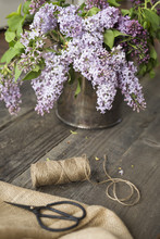 Flowers In A Vase By String With Burlap And Scissors On Wooden Table