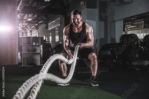 Photo Muscular powerful aggressive man working out with rope in functional training fi
