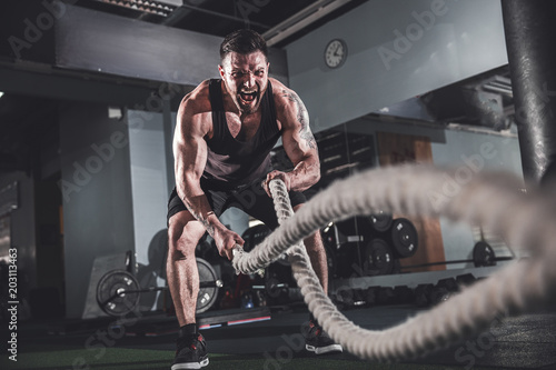 Fototapeta  Muscular powerful aggressive man working out with rope in functional training fi