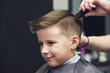 European boy getting hairstyle in barbershop.