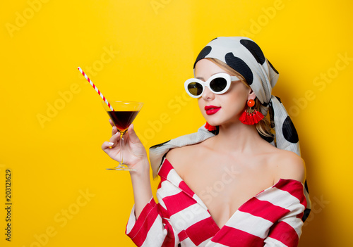 Fototapety, obrazy: Portrait of beautiful style woman in sunglasses and striped clothes with cocktail glass on yellow background