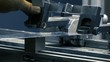 Industrial worker operates with hydraulic bending machine on the factory. Close-up shot. Metal working concept