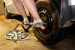Mechanician changing car wheel in garage. Man exchanging tire. Tire service. Tire fitting.