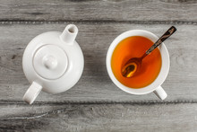 Table Top View On Small White Teapot And Cup Full Of Hot Amber Tea With Silver Spoon In It, Placed On Gray Wood Table.
