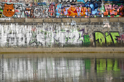 Tattoo graffiti writer finishing his paint in urban river contest - Contemporary artist at work - Lifestyle, street art concept - © robin_ph