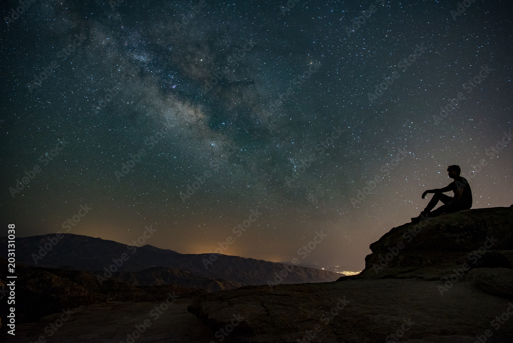Fototapety, obrazy: Milky way sky on the mountain with a silhouette of a person sitting on a rock