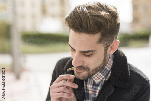 Handsome man smoking cigar in street