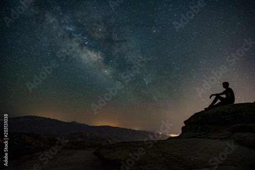 Fotografie, Tablou  Milky way sky on the mountain with a silhouette of a person sitting on a rock