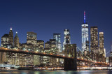 Fototapeta Nowy York - Brooklyn Bridge and the illuminated Skyline of Manhattan in the evening with blue sky and smooth water surface shot from Brooklyn side, New York, Usa.