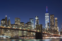 Brooklyn Bridge And The Illuminated Skyline Of Manhattan In The Evening With Blue Sky And Smooth Water Surface Shot From Brooklyn Side, New York, Usa.