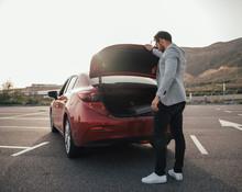Man Traveler Putting Suitcase In Car Trunk