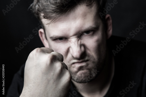 Photo Portrait of an angry man clenching his fist on a black background