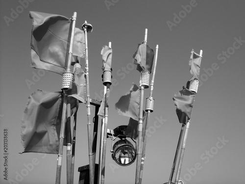 Wehende Fahnen im Wind mit Scheinwerfer auf einem alten Fischerboot am Strand von Binz auf Rügen an der Ostsee in Mecklenburg-Vorpommern, fotografiert in neorealistischem Schwarzweiß