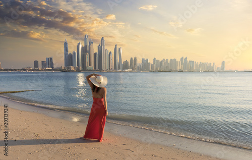 Wall Murals Dubai Beautiful woman with a red dress and a white hut is walking on the beach in Dubai. In the background there is the skyline from Dubai Marina