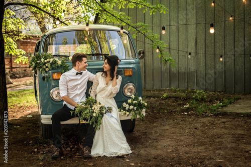 Cheerful happy young couple sit on the bumper retro-minibus. Wallpaper Mural