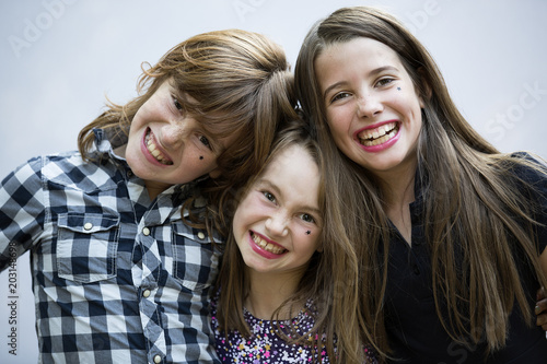 Portrait of cheerful siblings standing against white background