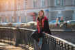 A pretty girl sits on the railing of the canal embankment in St. Petersburg.