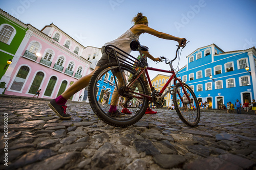 Foto  Unrecognizable woman pushing a bike passes in front of colorful colonial architecture on a broad cobblestone hill in the historic city center of Pelourinho