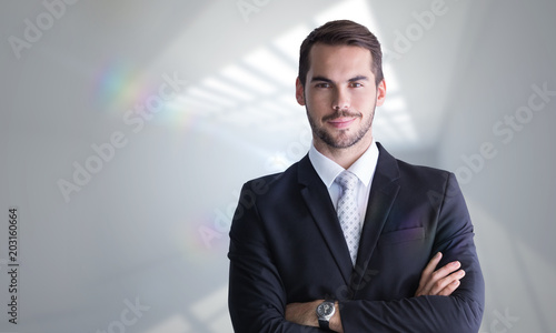 Fototapety, obrazy: Smiling businessman posing with arms crossed against room with windows at ceiling