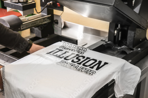 Fotografie, Obraz  Young man printing on t-shirt at workshop