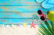 Summer background - top view of beach sand with slipper, coconut, sunglasses, starfish, shells, coral and bracelet made of seashells on blue wooden background. Summer concept, Vintage retro styles
